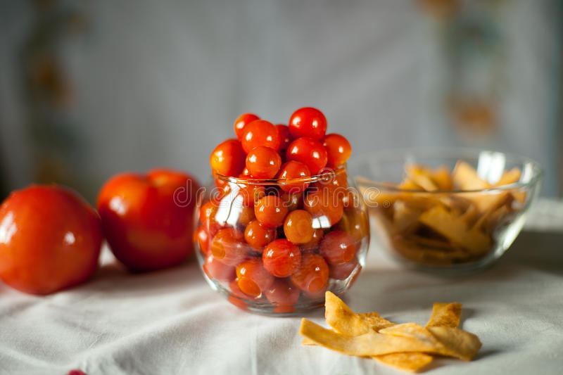 Pequeños tomates de cereza preservados en un florero de cristal imagen de archivo libre de regalías