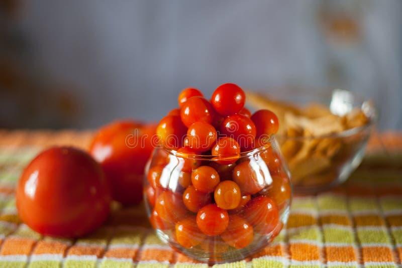 Pequeños tomates de cereza preservados en un florero de cristal fotografía de archivo libre de regalías