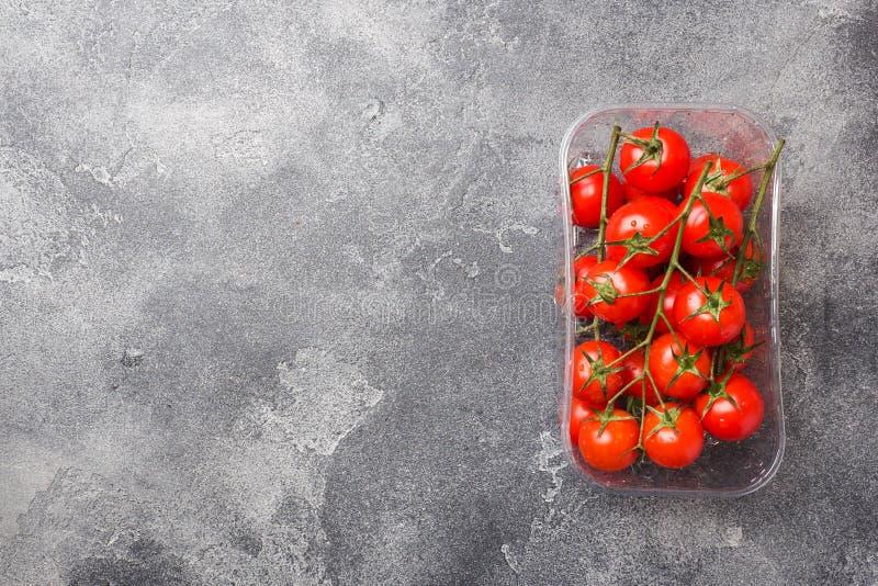 Pequeños tomates de cereza rojos en la tabla oscura, visión superior Copie el espacio fotos de archivo libres de regalías