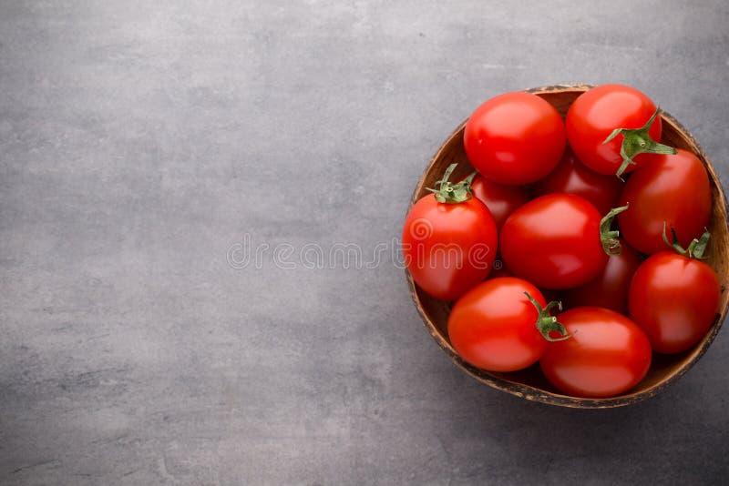 Pequeños tomates de ciruelo en un cuenco de madera en un fondo gris fotografía de archivo libre de regalías