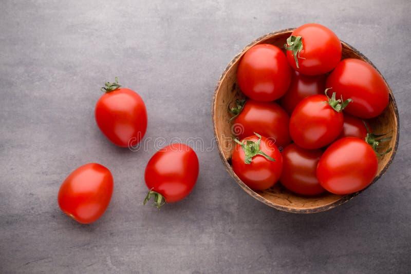 Pequeños tomates de ciruelo en un cuenco de madera en un fondo gris fotos de archivo