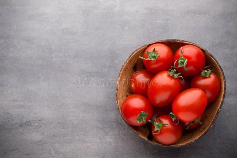 Pequeños tomates de ciruelo en un cuenco de madera en un fondo gris imagenes de archivo
