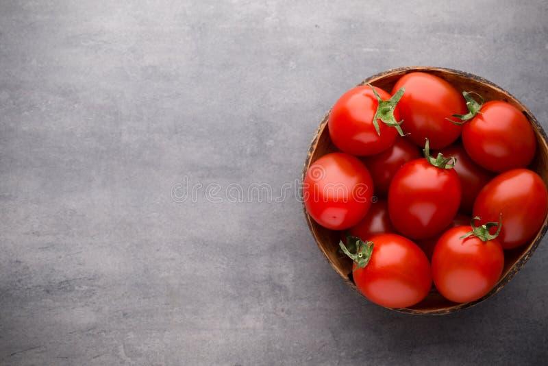 Pequeños tomates de ciruelo en un cuenco de madera en un fondo gris imagen de archivo