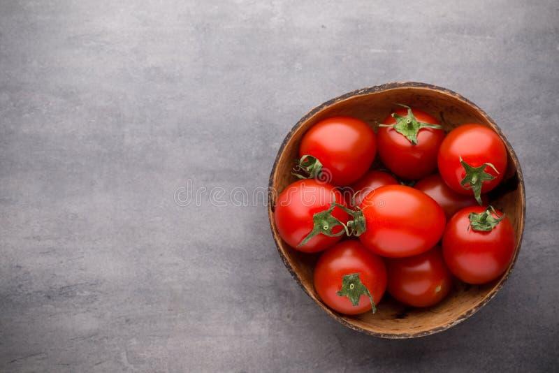 Pequeños tomates de ciruelo en un cuenco de madera en un fondo gris foto de archivo libre de regalías