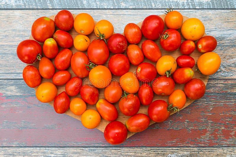 Pequeños tomates dispuestos en forma del corazón fotos de archivo