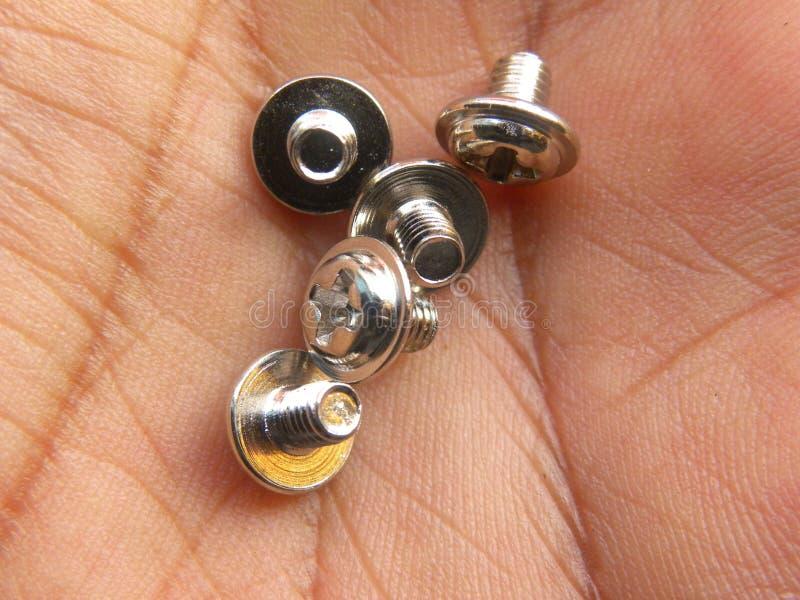 Pequeños tornillos de metal en la palma de la mano fotos de archivo