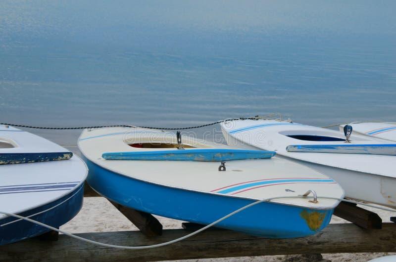 Pequeños veleros huecos del bote de la navegación del estilo del tablero del cuerpo en los estantes foto de archivo
