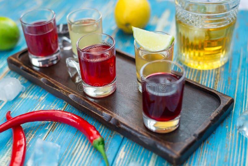Pequeños vidrios con las bebidas coloridas en un tablero de madera imágenes de archivo libres de regalías