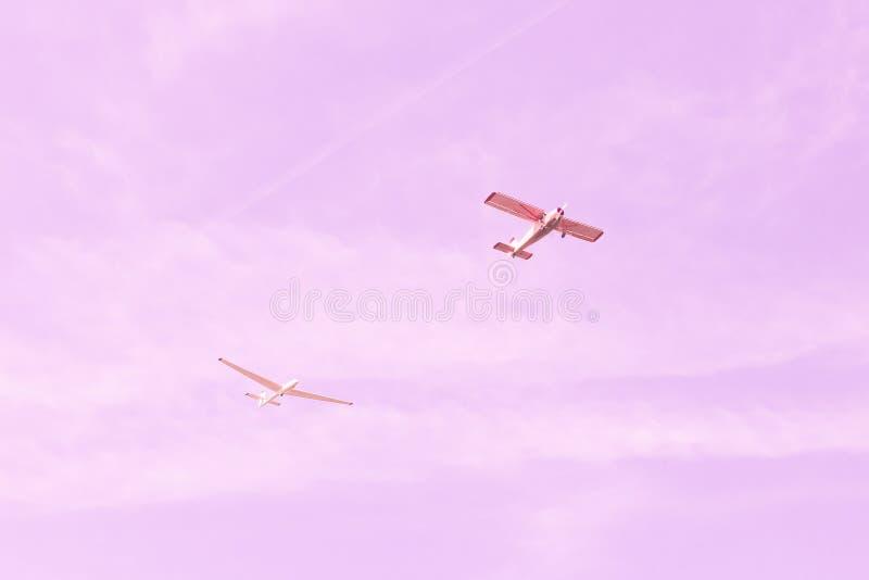 Pequeños viejos avión del vintage y vuelo monomotores contra el cielo rosado, concepto del planeador de trabajo en equipo, sueño, imagen de archivo libre de regalías