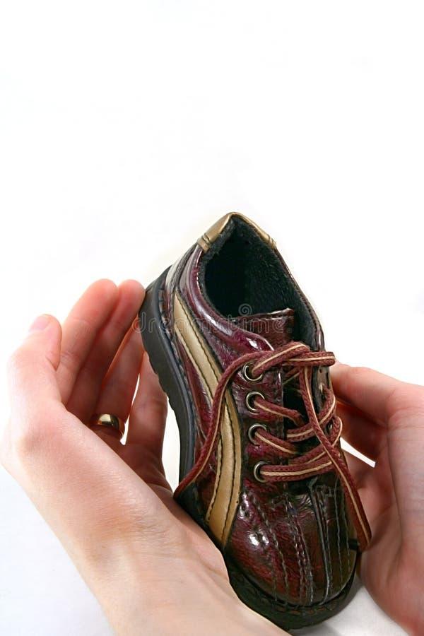 Pequeños zapato de bebé y padres h imagen de archivo libre de regalías