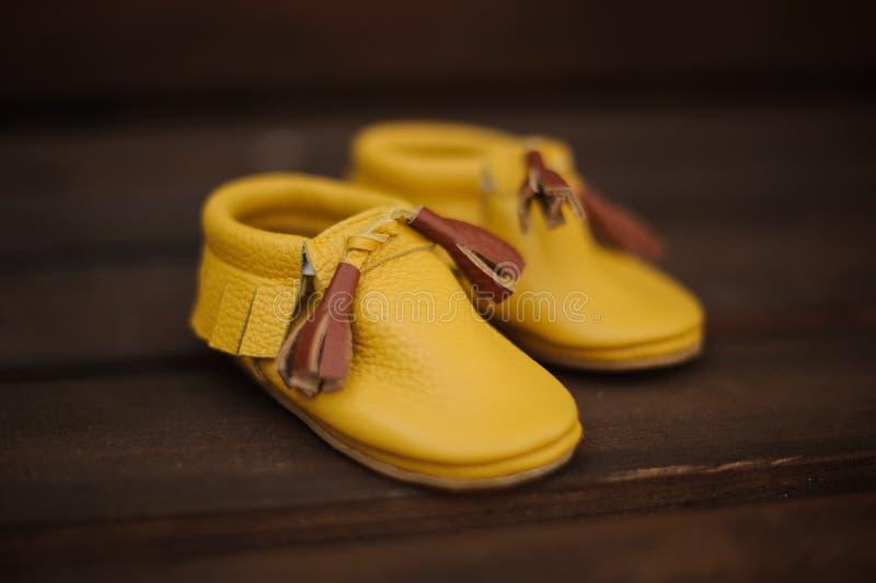 Pequeños zapatos amarillos lindos del niño con el cordón marrón fotografía de archivo