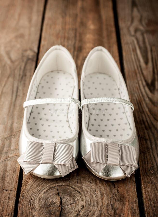 Pequeños zapatos de ballet de la plata de la muchacha en la madera rústica del vintage fotografía de archivo