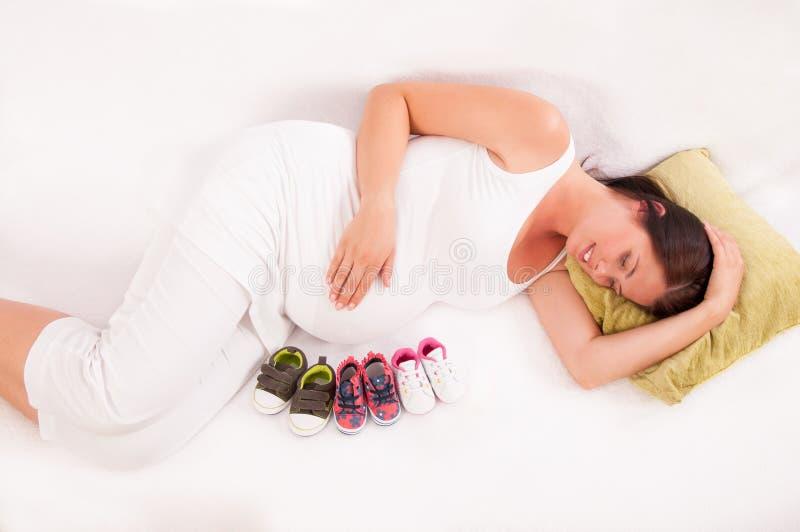 Pequeños zapatos enfrente del vientre de w embarazada imagenes de archivo