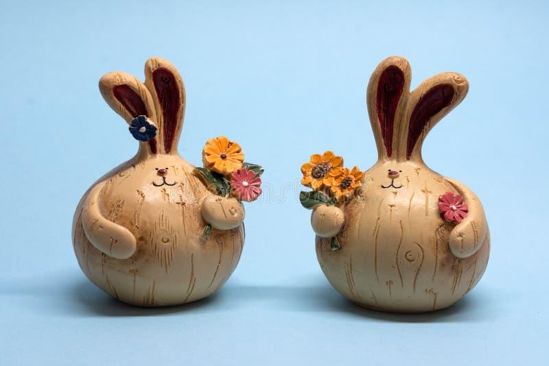 Peque?as figuras de dos liebres con las flores en un fondo azul imágenes de archivo libres de regalías