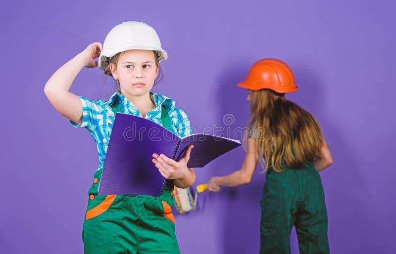 peque?as muchachas que reparan junto en taller D?a del Trabajo 1 DE MAYO dirigir idea Carrera futura Ni?os en casco imágenes de archivo libres de regalías
