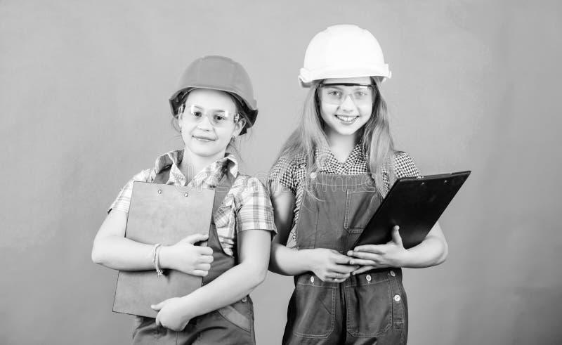 peque?as muchachas que reparan junto en taller Profesi?n futura Arquitecto del ingeniero del constructor Trabajador del ni?o en c foto de archivo