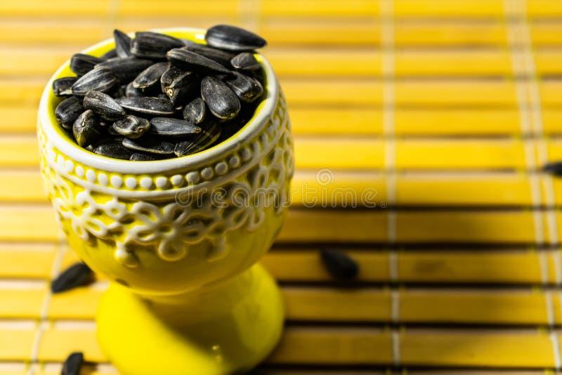 Peque?as semillas de girasol negras Haga clic las semillas con las c?scaras Un pu?ado en un soporte miniatura amarillo en una ser imagen de archivo libre de regalías
