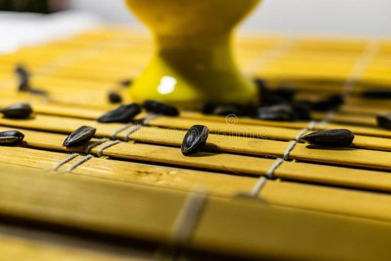 Peque?as semillas de girasol negras Haga clic las semillas con las c?scaras Un pu?ado en un soporte miniatura amarillo en una ser foto de archivo