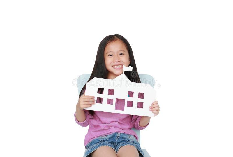 Peque?a escuela asi?tica sonriente del papel de la maqueta de la tenencia de la muchacha del ni?o que se sienta en la silla del n fotografía de archivo