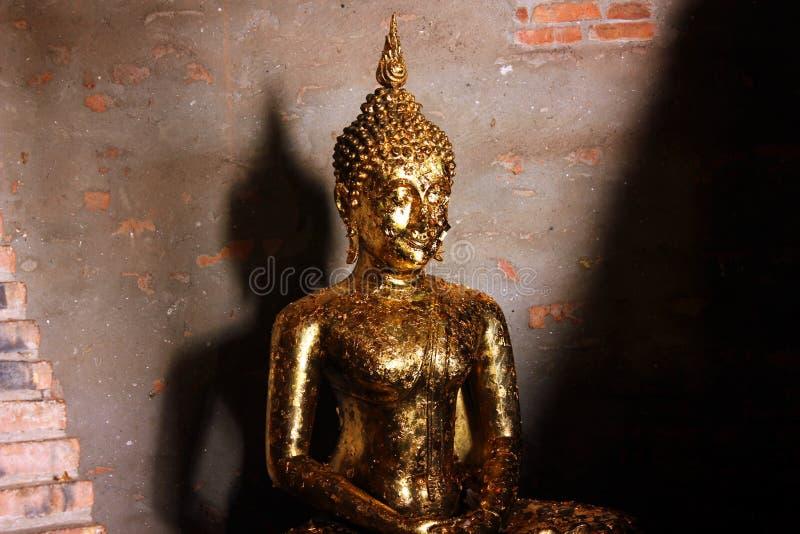 Peque?a escultura de Buda con el ofrecimiento del phra de oro del wai de las hojas en Ayutthaya, Tailandia fotografía de archivo