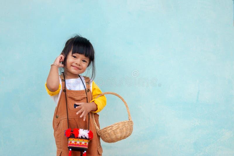 Peque Muchacha asiática linda en una sonrisa brillante y sostener del vestido marrón del babero una cesta de madera imagen de archivo libre de regalías
