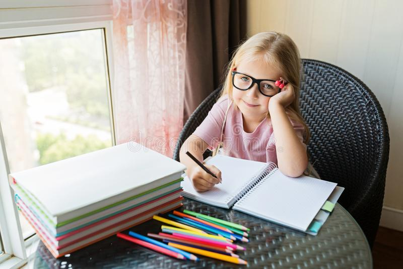 Peque?a muchacha cauc?sica linda que hace la preparaci?n y que escribe un papel El ni?o goza el aprender con felicidad en casa Li imágenes de archivo libres de regalías