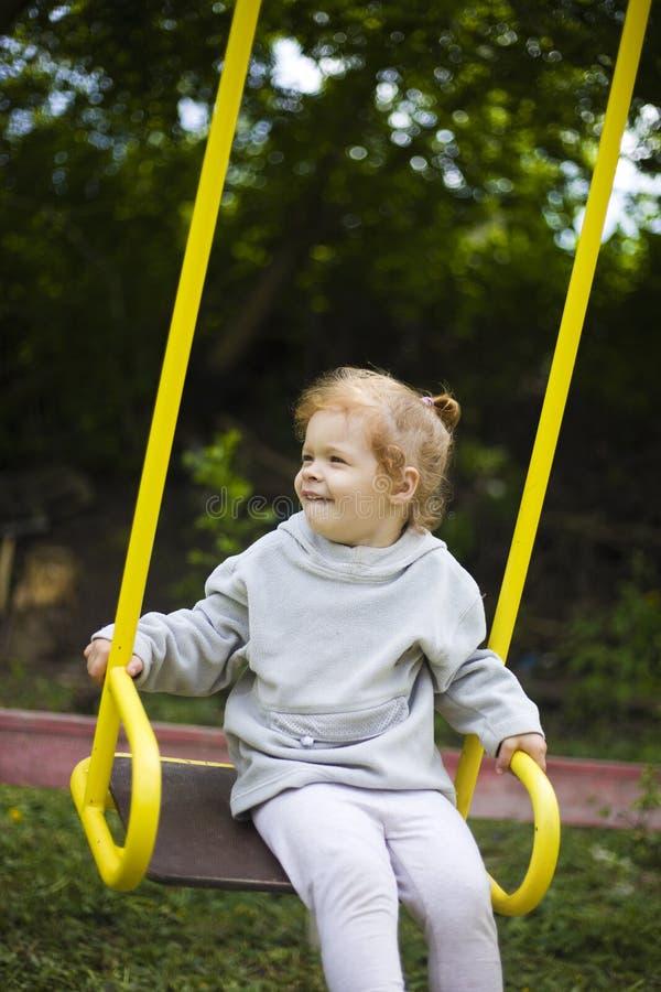 Peque?a muchacha hermosa del pelirrojo que monta un oscilaci?n en el patio fotos de archivo libres de regalías