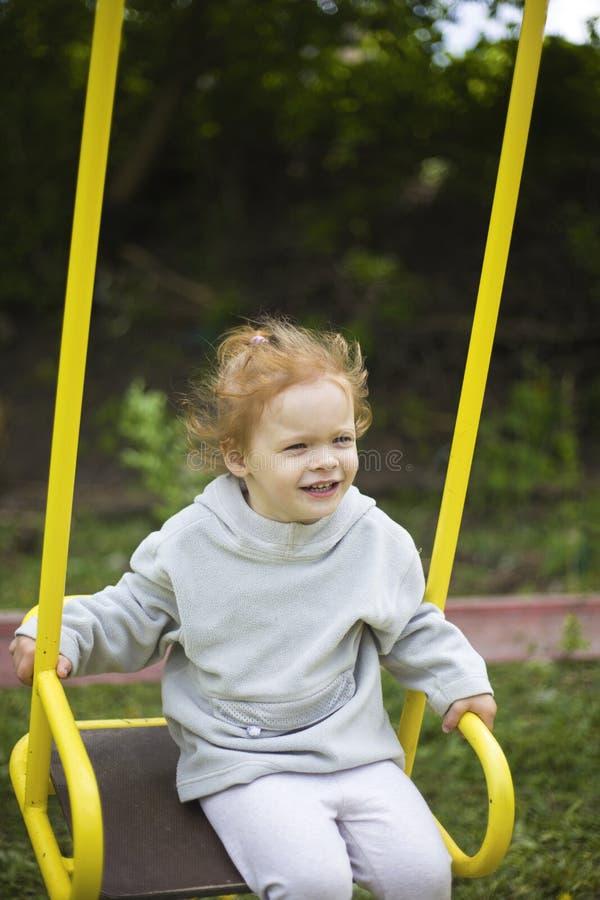 Peque?a muchacha hermosa del pelirrojo que monta un oscilaci?n en el patio foto de archivo libre de regalías