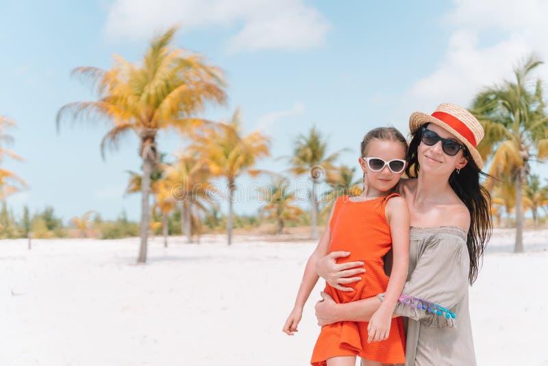 Peque?a muchacha linda y madre joven en la playa tropical imagen de archivo