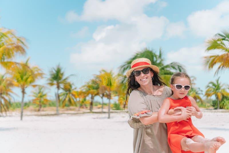 Peque?a muchacha linda y madre joven en la playa tropical foto de archivo