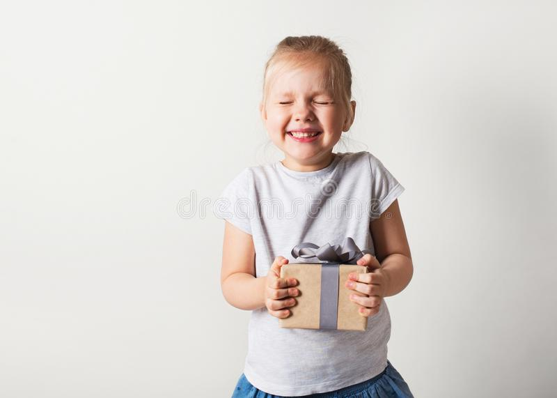 Peque?a muchacha sonriente bonita con la caja de regalo en el fondo blanco imagen de archivo