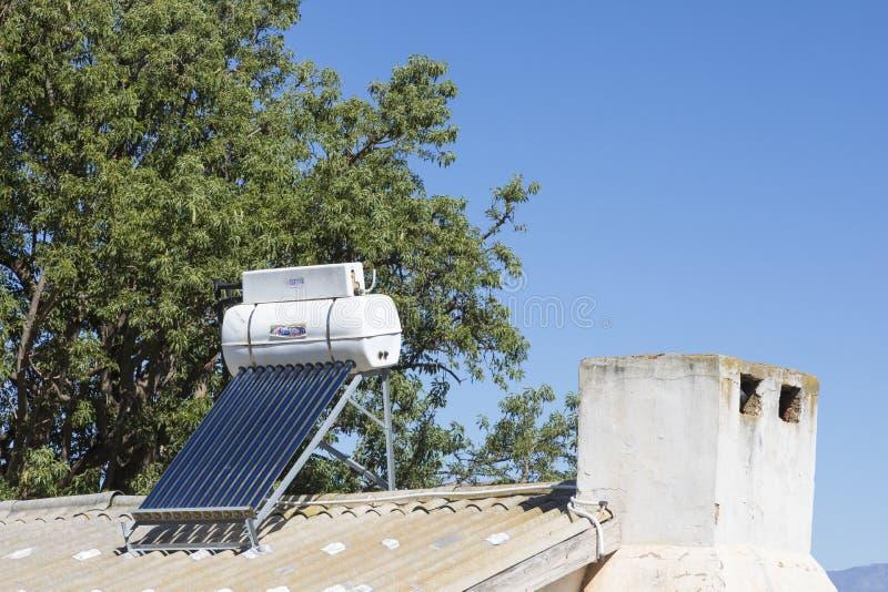 Peque?o g?iser solar de la agua caliente y el panel fotovoltaico en una caba?a rural de los trabajadores de granja imágenes de archivo libres de regalías