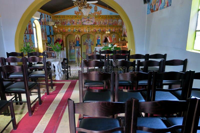 Peque?o interior de la iglesia con los iconos y las sillas en Europa imagen de archivo