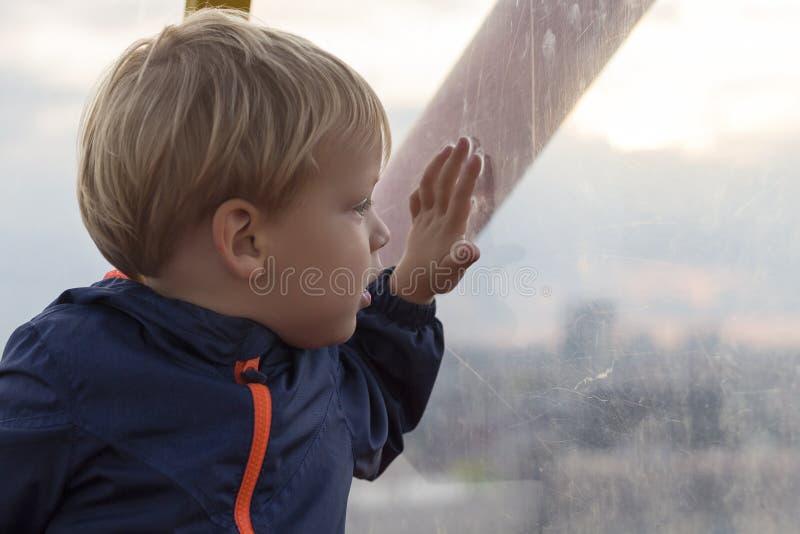 Peque?o muchacho rubio adorable del ni?o que se sienta cerca de ventana y que parece exterior fotografía de archivo