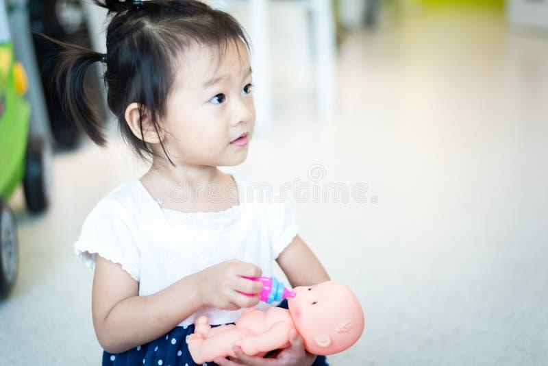 Peque?o ni?o asi?tico dulce del beb? que juega la mu?eca, leche de la botella de alimentaci?n a la mu?eca fotografía de archivo libre de regalías