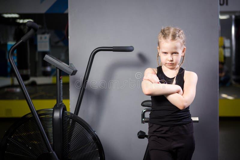 Peque?o ni?o cauc?sico atractivo que usa la bicicleta est?tica en el gimnasio Aptitud Un peque?o atleta que usa una bici del aire imagen de archivo libre de regalías