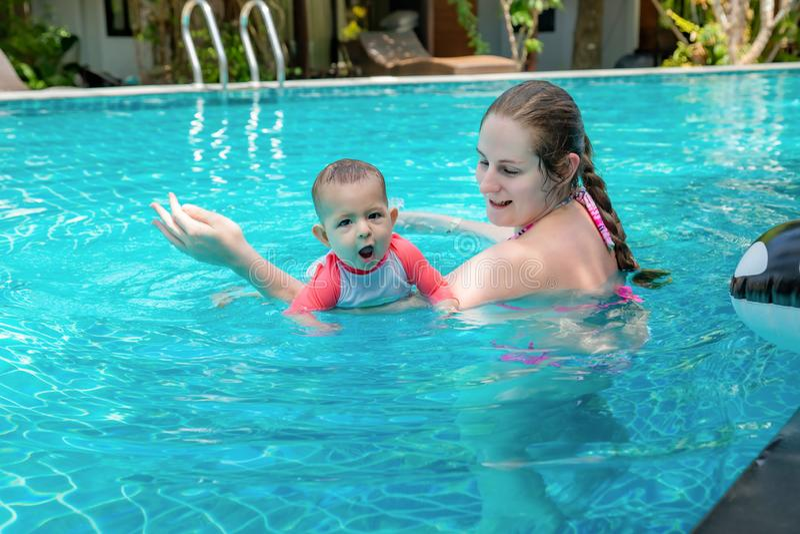 Peque?o ni?o feliz con la madre, primera vez del beb? en una piscina grande y muy impresionada Muy feliz infantil, con la boca ab fotografía de archivo libre de regalías