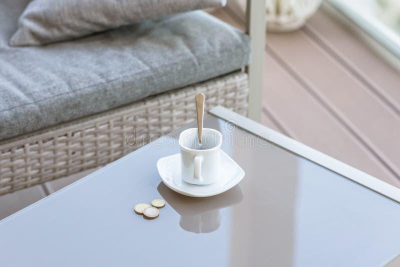 Pequena alteração em um euro e xícara de café vazia em uma tabela de vidro do café exterior Pagamento, ponta imagem de stock royalty free