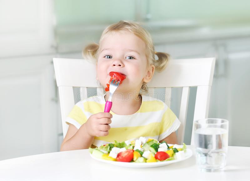 Pequena criança comendo comida saudável salada em casa imagens de stock