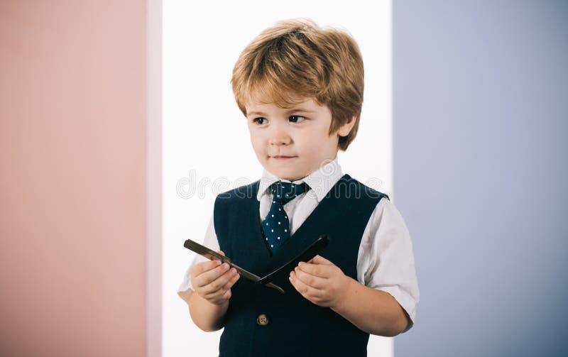 Pequeno barbeiro O garoto segura uma lâmina de barba Assistente de Barbershop Futuro Muschin Bebê com uma lâmina Como ensinar uma fotos de stock royalty free