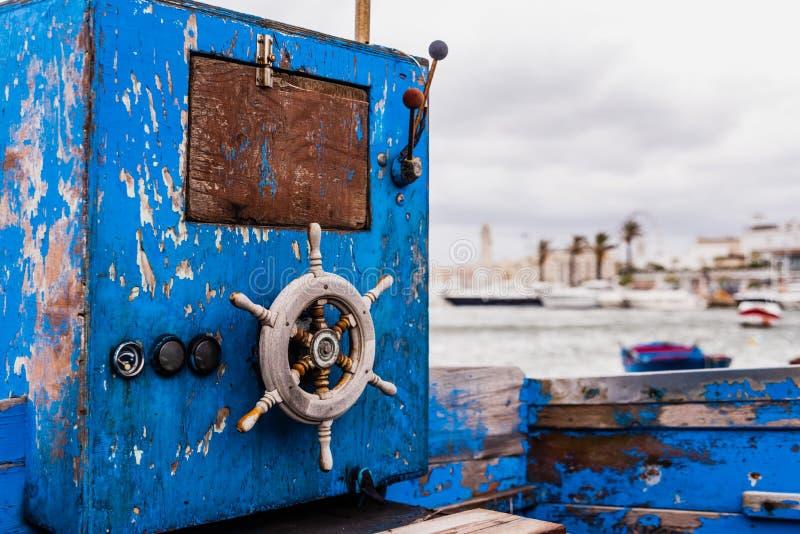 Pequeno leme de madeira de um barco embraiado envelhecido e abandonado à beira do mar fotografia de stock