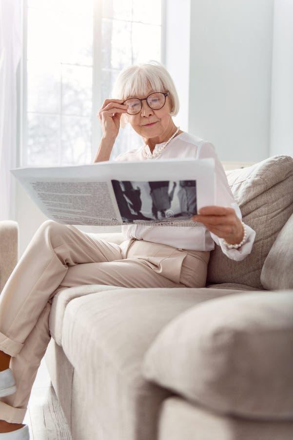 Pequeno senhora idosa que ajusta vidros ao ler o jornal foto de stock royalty free