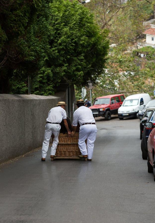 Pequeno trenó tradicional movente do bastão dos cavaleiros do Toboggan para baixo nas ruas de Funchal Parque de Monte, ilha de Ma foto de stock