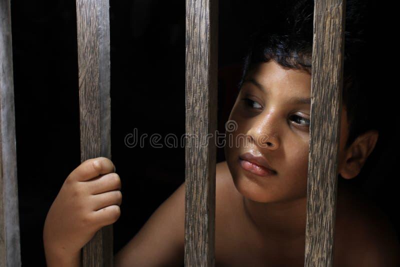 Pequeno triste olhar da janela Retrato de uma triste criança inocente olhando pela janela fotos de stock royalty free