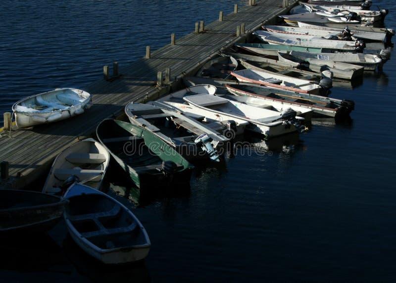 Pequenos, os barcos a motor amarraram a uma doca de madeira fotos de stock royalty free