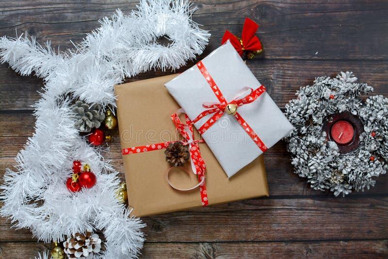 Pequenos presentes embalados em papel artesanal e diversas decorações de Natal em fundo de madeira imagens de stock