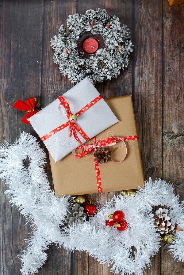Pequenos presentes embalados em papel artesanal e diversas decorações de Natal em fundo de madeira fotos de stock