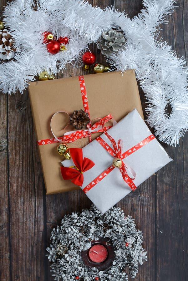 Pequenos presentes embalados em papel artesanal e diversas decorações de Natal em fundo de madeira imagem de stock royalty free