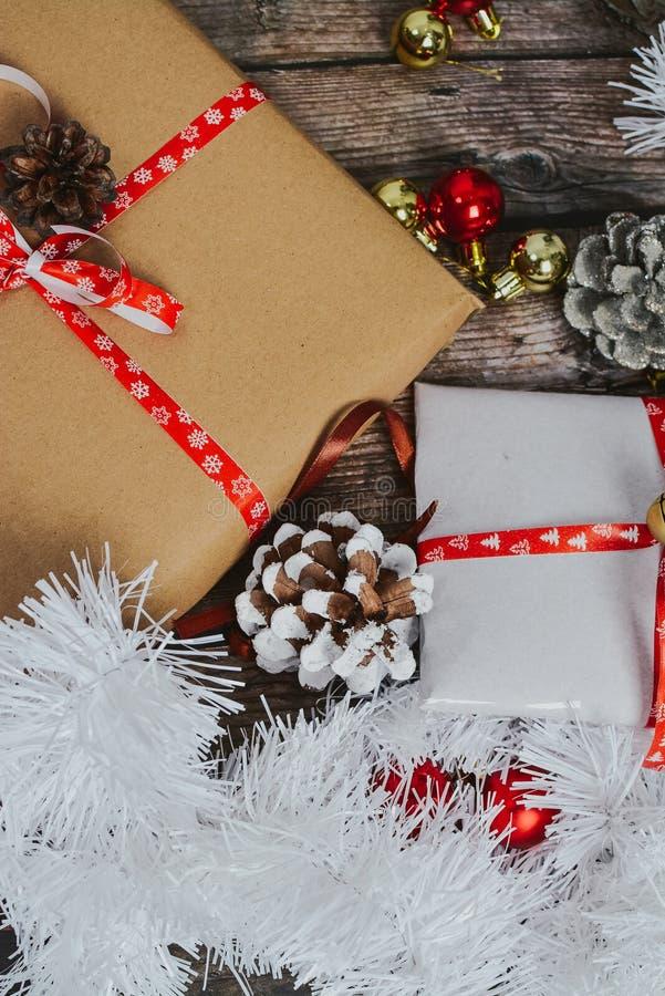 Pequenos presentes embalados em papel artesanal e diversas decorações de Natal em fundo de madeira imagens de stock royalty free
