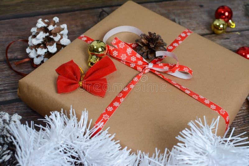 Pequenos presentes embalados em papel artesanal e diversas decorações de Natal em fundo de madeira foto de stock royalty free